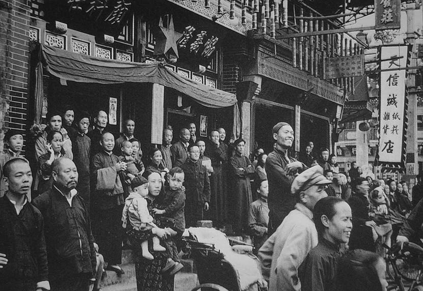 Local people gaze out into the distance from the street in front of a line of shops when PLA soldiers enter the city, in Beijing, spring of 1949. Courtesy of 'Old Photos'
