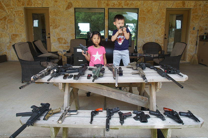 The children of two Joy One World clients pose with pistols before an array of firearms in the U.S., July 22, 2017. Courtesy of Joy One World